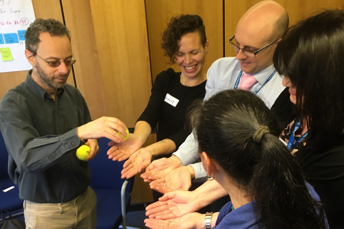 Parents and staff holding out their hands during a workshop in Bromley