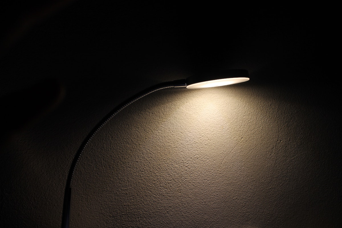 A lamp lit against a blank wall casting shadows