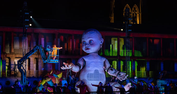 A giant baby model the size of a double decker bus lit up on stage with actors surrounding it