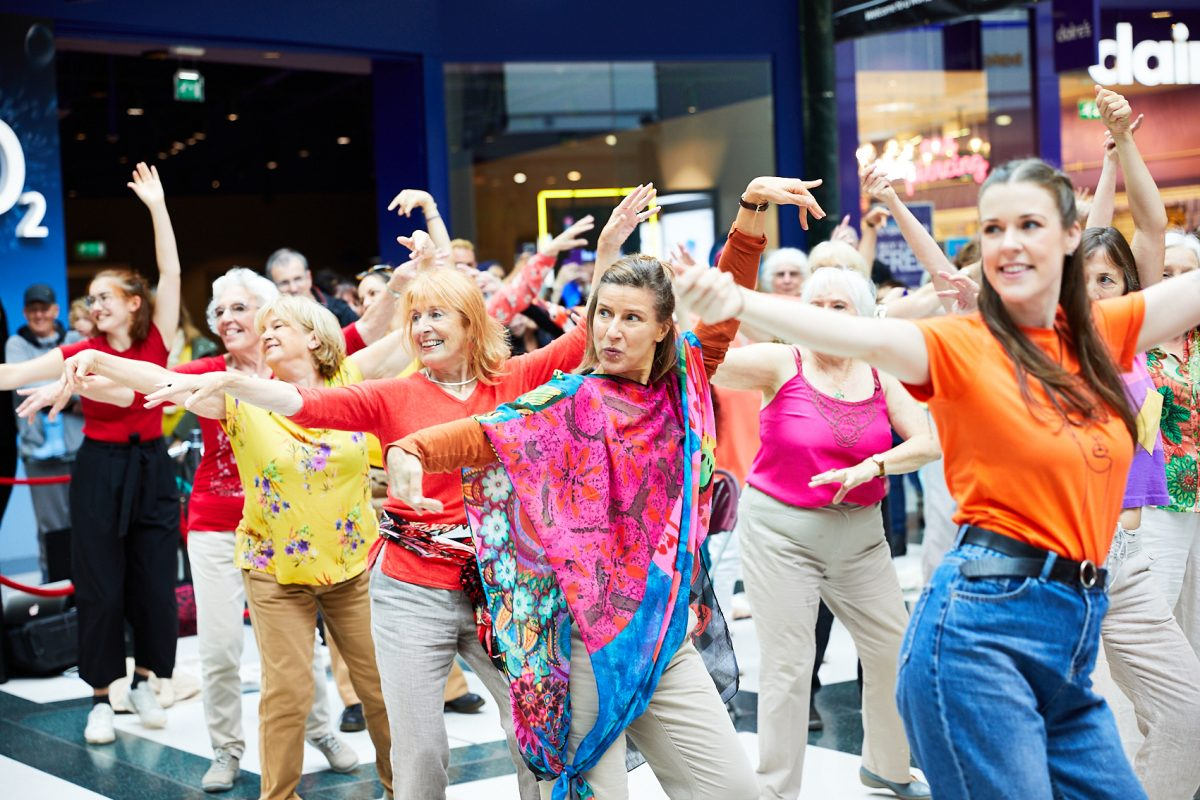 A group of women of different ages dressed in colourful clothing dancing together