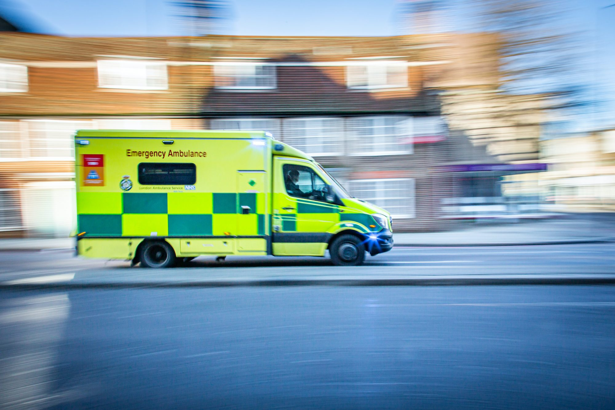 An ambulance driving down a residential street