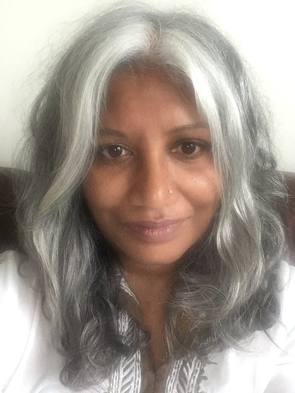 Image of a smiling woman with long silver wavy hair.