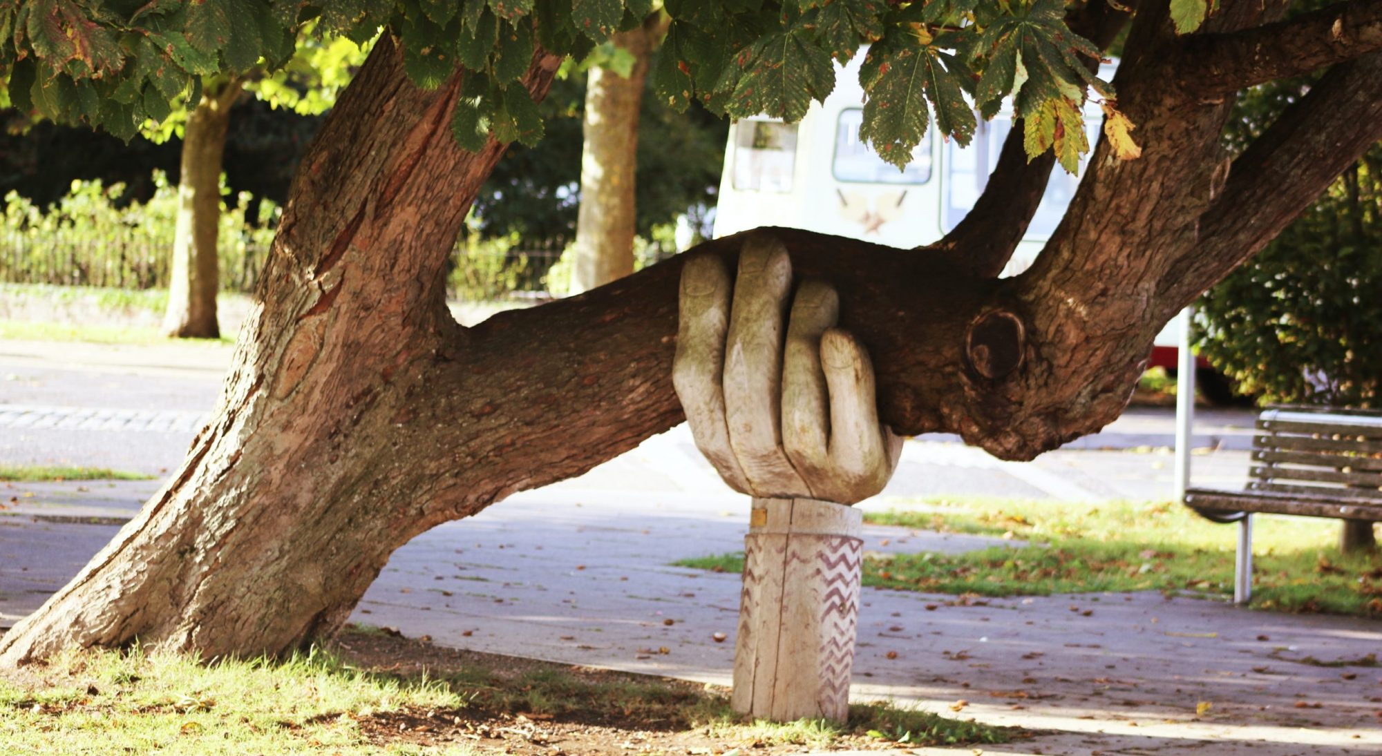 A carved wooden hand holds up the heavy branches of a tree.