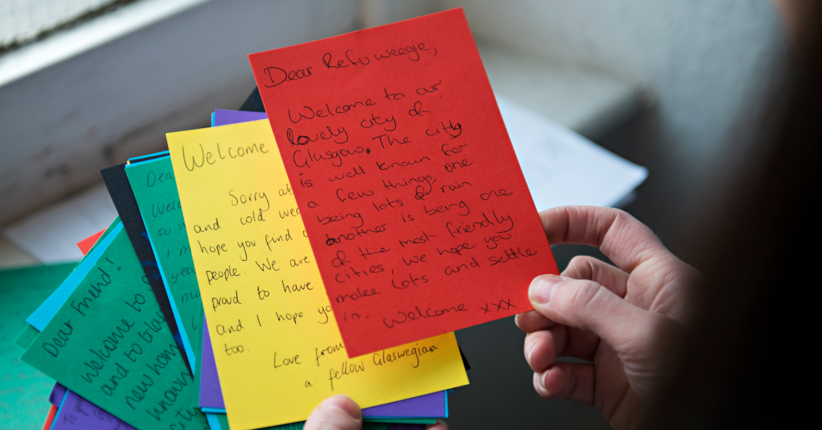 A hand holds a series of colourful, handwritten welcome notes