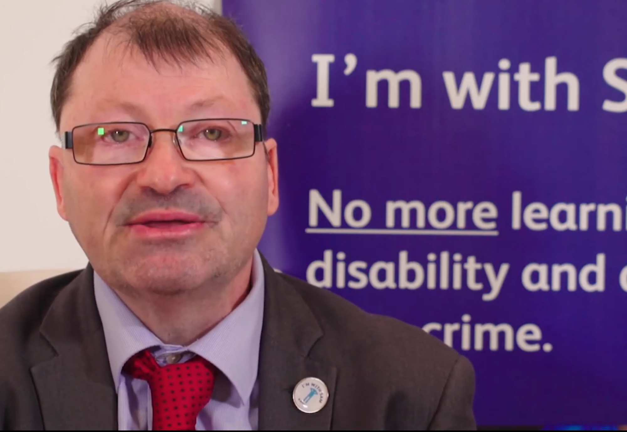 A man in a suit and tie speaks directly into camera. Behind him is an I'm With Sam campaign display against learning disability hate crime.